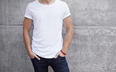 guy in white t short stood against brick wall