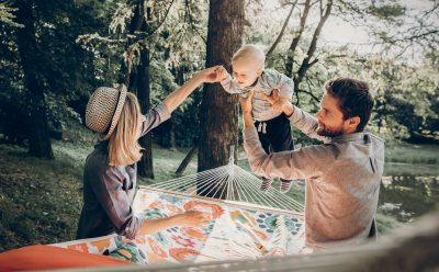 young family playing with son on hammock
